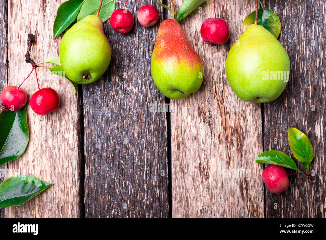 Pear and small apple on wooden rustic background. Top view. Frame. Autumn harvest. Copy space - Stock Image
