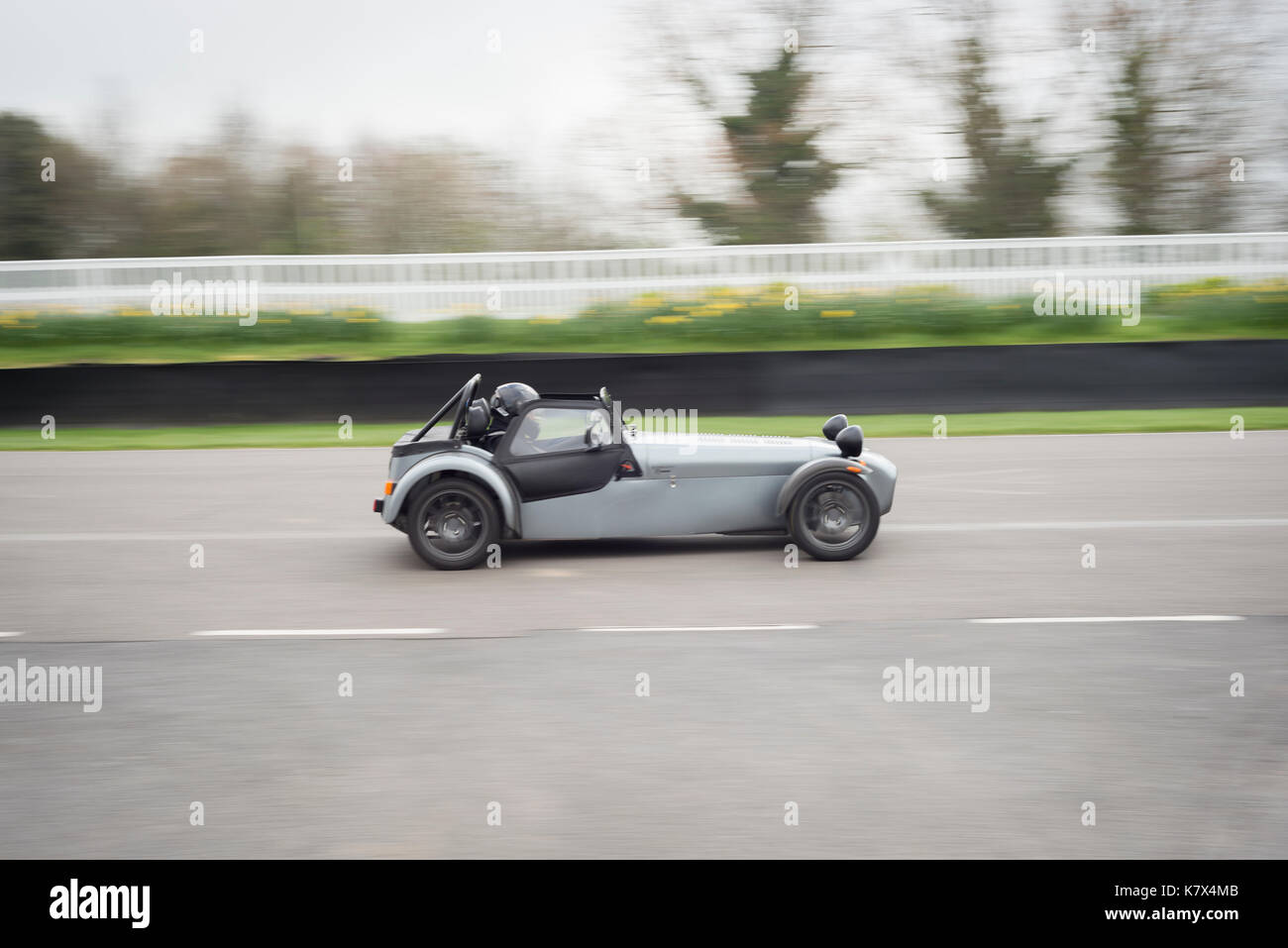 Fast car on racetrack at Goodwood with motion blur - Stock Image