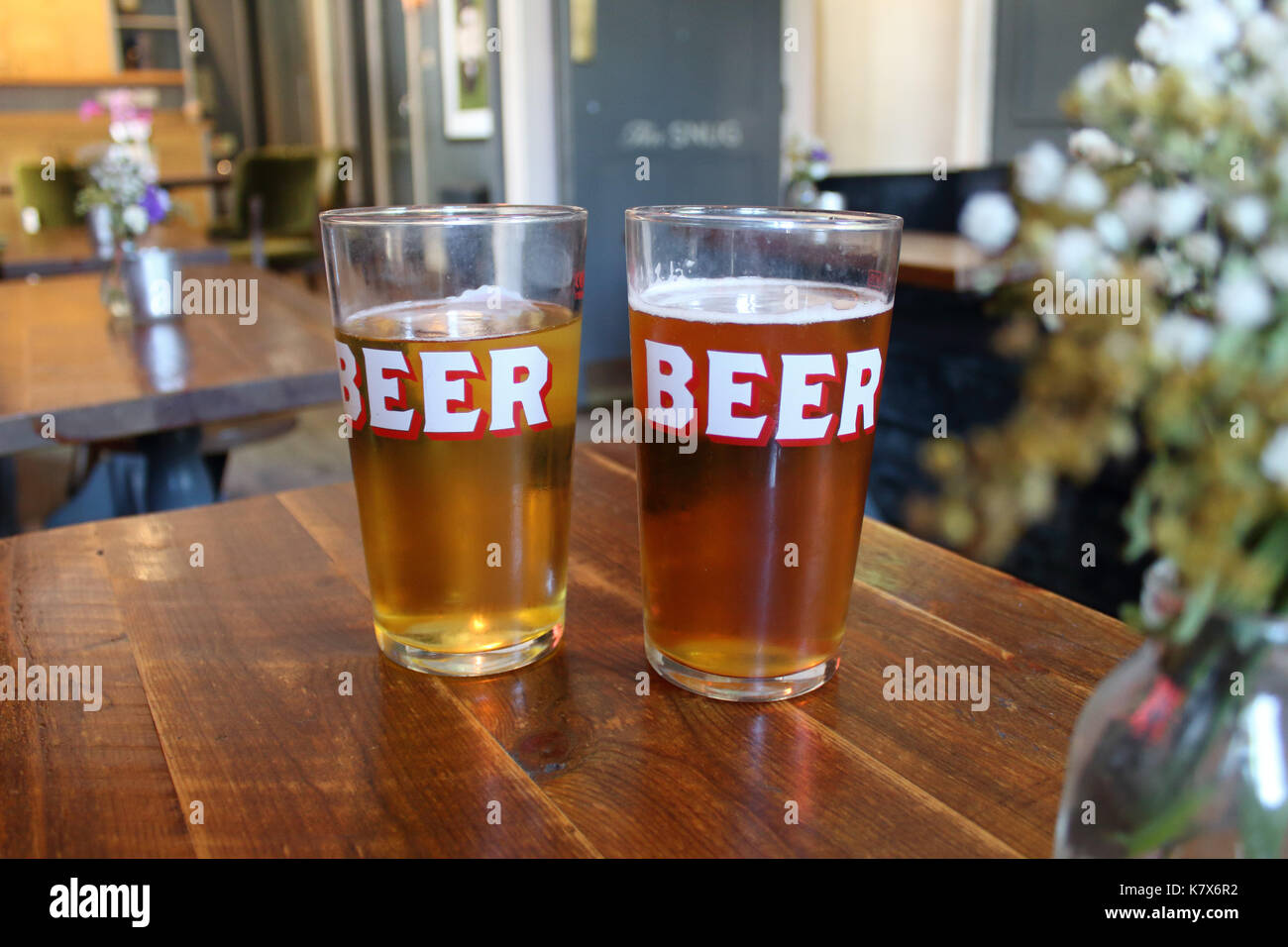 Two pints in 'BEER' glasses in a pub. Shallow focus on glasses. London, UK. - Stock Image