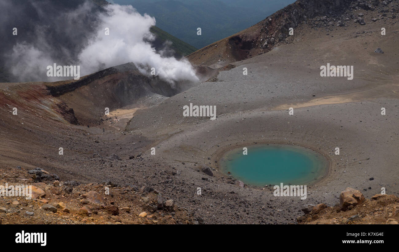 Horizontal shot of rim of volcano with turquoise blue crater pond in foreground and white steam vent in background on sunny day.  Volcanic rock, ash. - Stock Image
