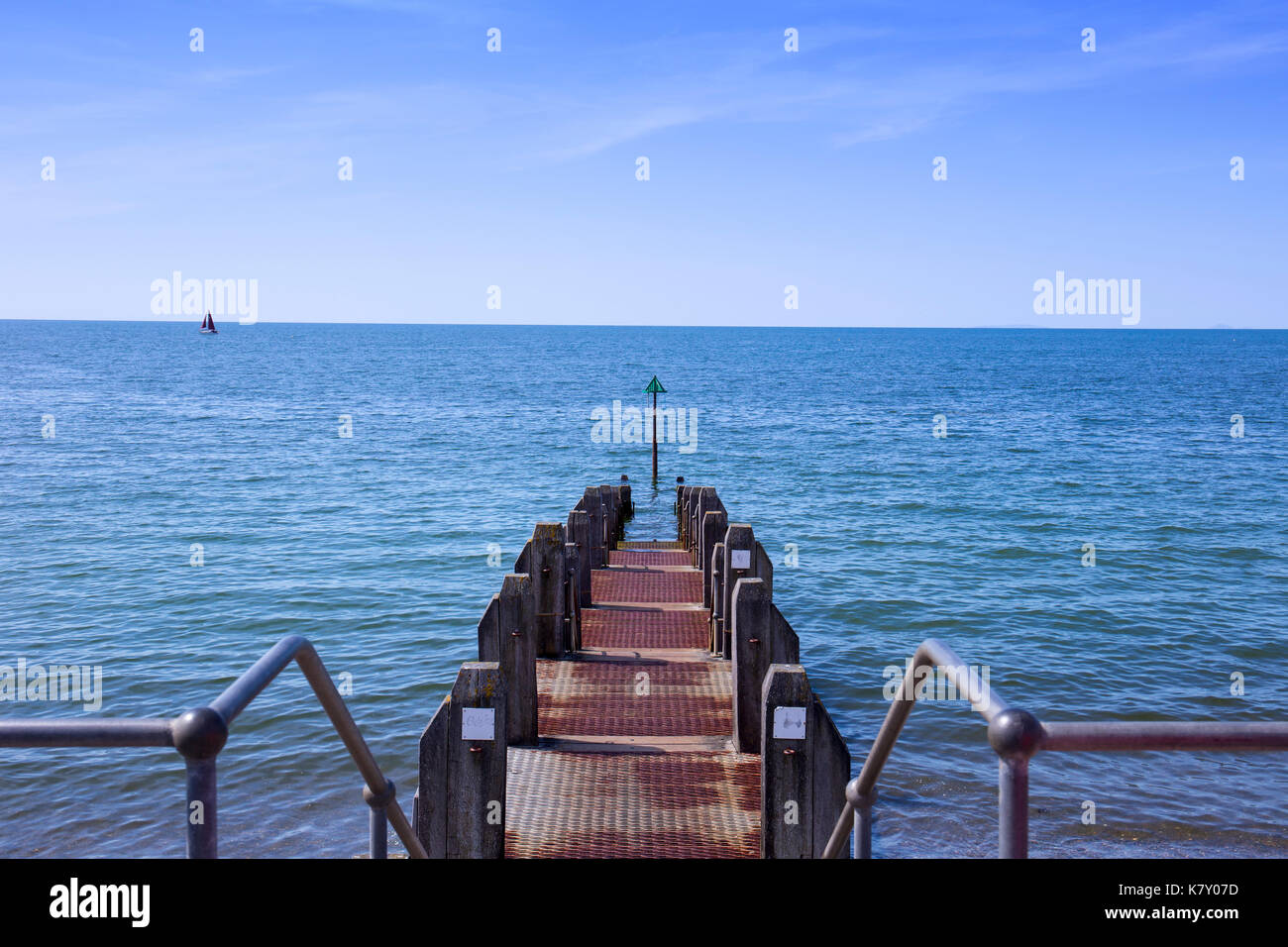 A sailboat on Cardigan bay with jetty in Aberystwyth Ceredigion Wales UK - Stock Image