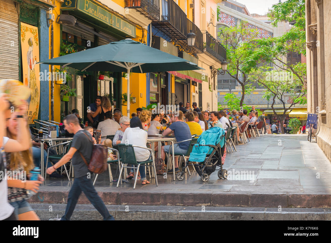 Valencia Spain street, people relax over lunch at street cafes sited near the Mercado Central in the old town - the Ciutat Vella - in Valencia, Spain. - Stock Image