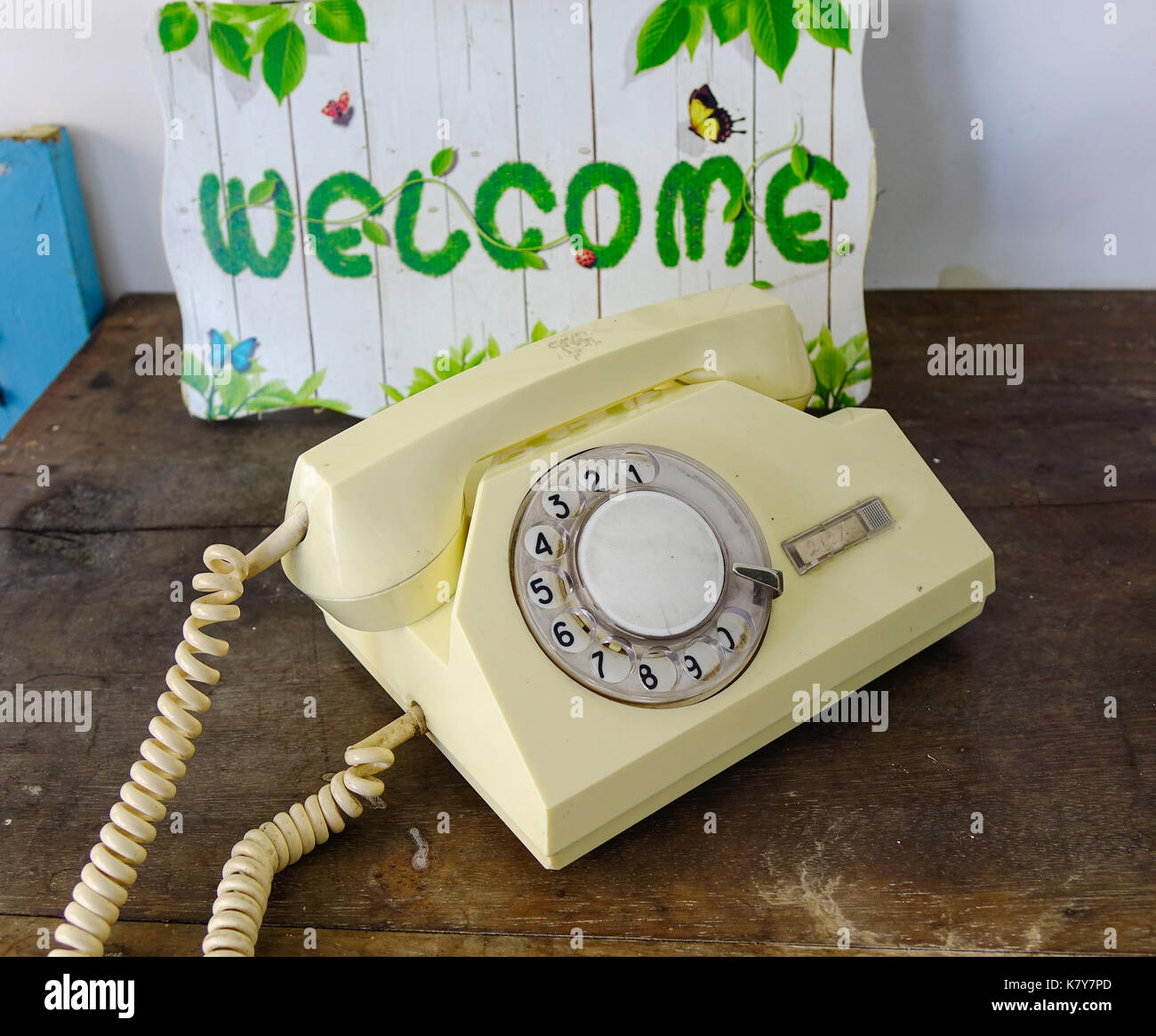 Retro Yellow Telephone On Wood Table With Welcome Board For