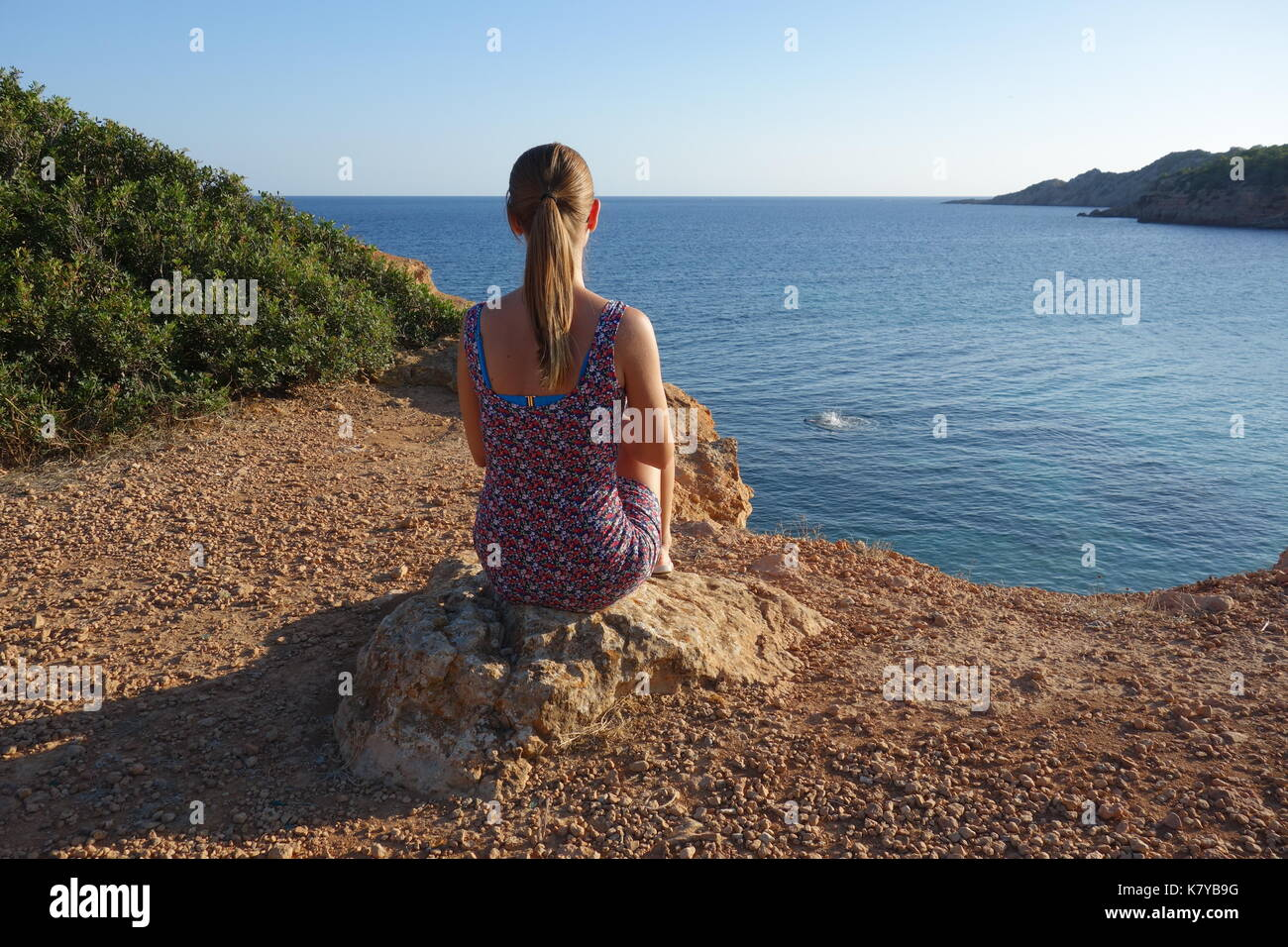 Blonde girl looking towards the beach of Cala sa Caleta or Bol Nou, Spain - Stock Image