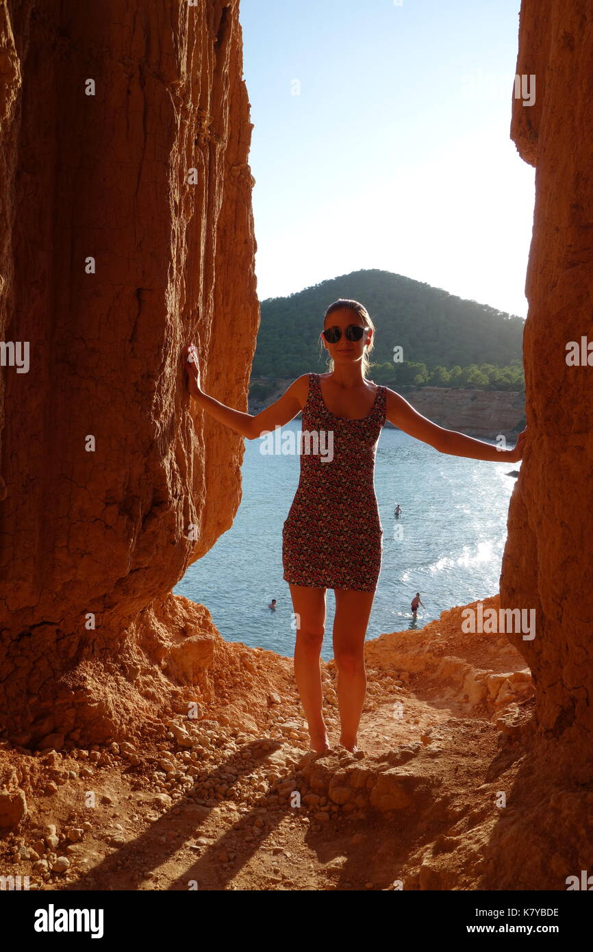 Tourist blonde girl visiting the cave listed as World Heritage by UNESCO of Sa Caleta or Bou Nou in Ibiza island, Spain. September 2017 - Stock Image