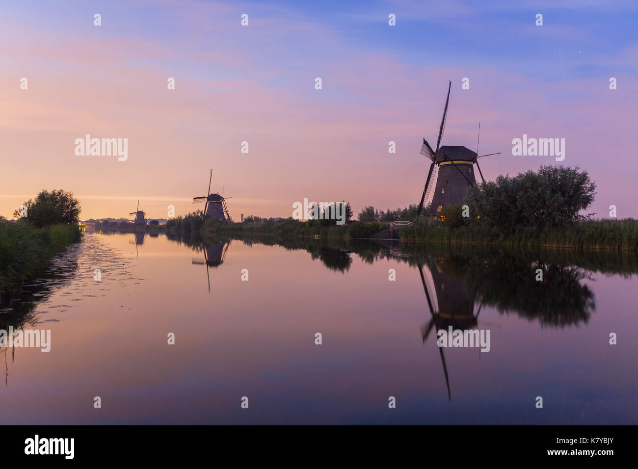 Windmills of Kinderdijk, a world heritage site of UNESCO, are lined up at the waterside at sunset. Besides windmills, the site shows various other fea - Stock Image