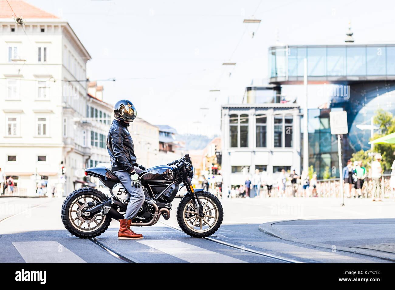 Cool looking motorcycle rider on custom made scrambler style cafe racer in the city - Stock Image