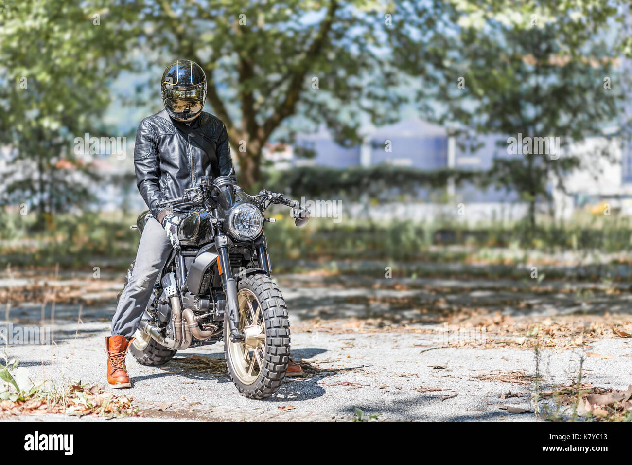 Cool looking motorcycle rider on custom made scrambler style cafe racer in the park - Stock Image