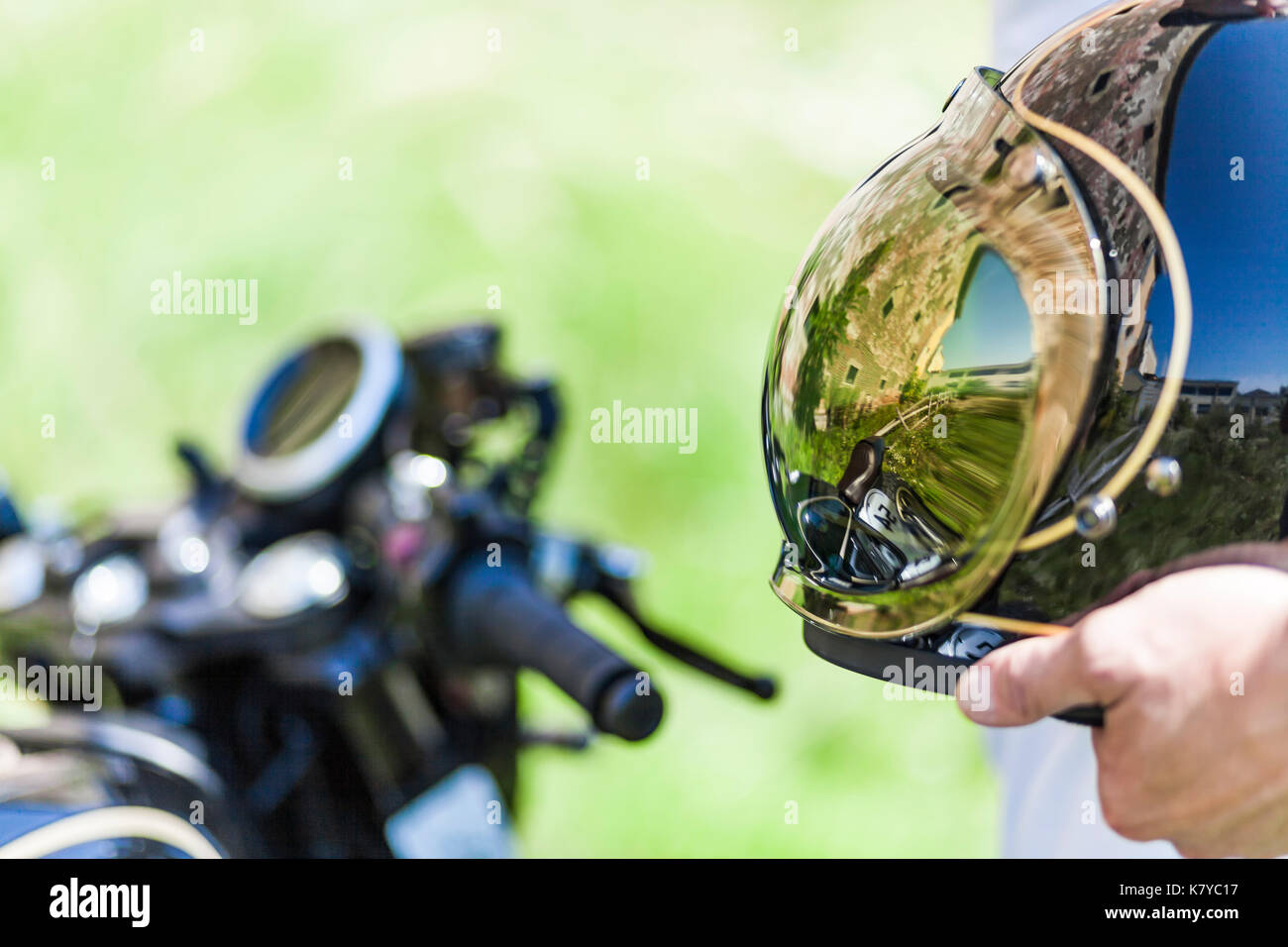 Cool reflection of custom made scrambler style cafe racer in the helmet - Stock Image