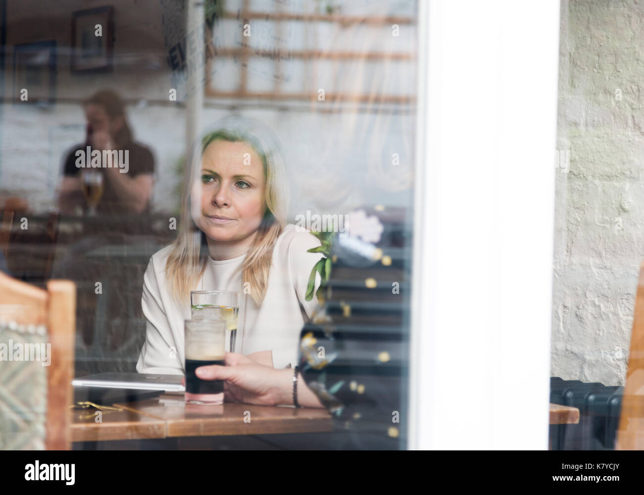 Pensive blonde attractive young adult single woman in pub. Shot through window with reflections on glass - Stock Image
