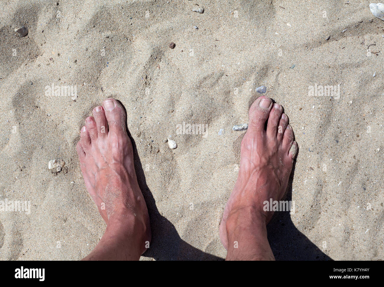 Details of man's legs, standing on sand. - Stock Image