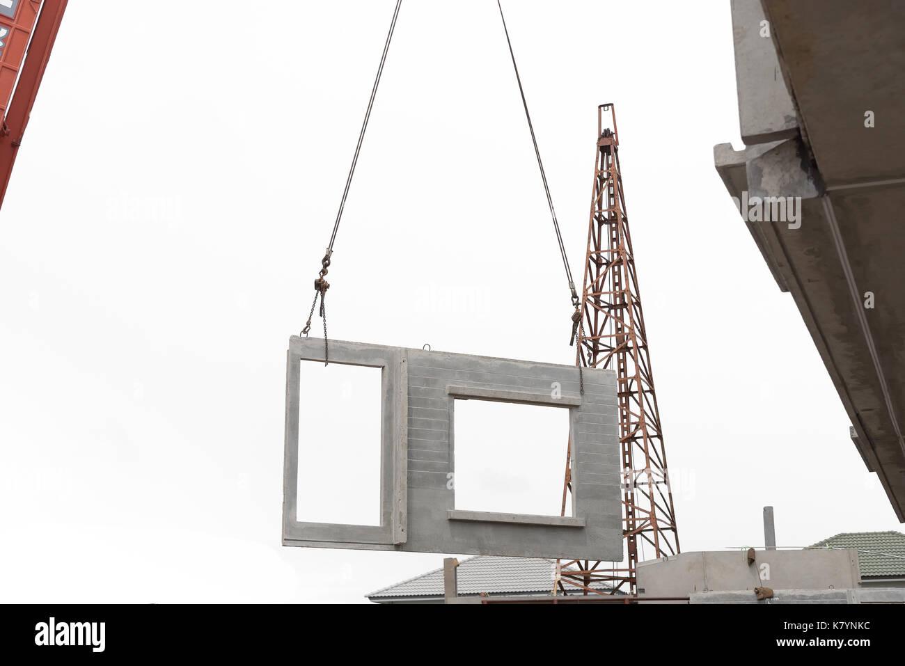 Construction site crane is lifting a precast concrete wall
