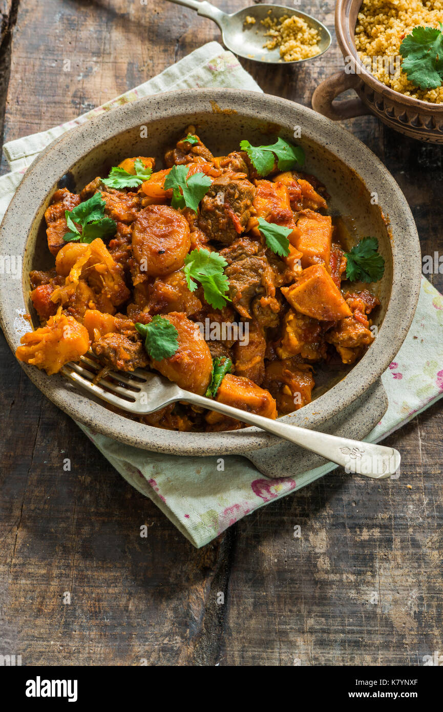 Maroccan lamb tajine with couscous garnished with fresh coriander leaves - high angle view - Stock Image
