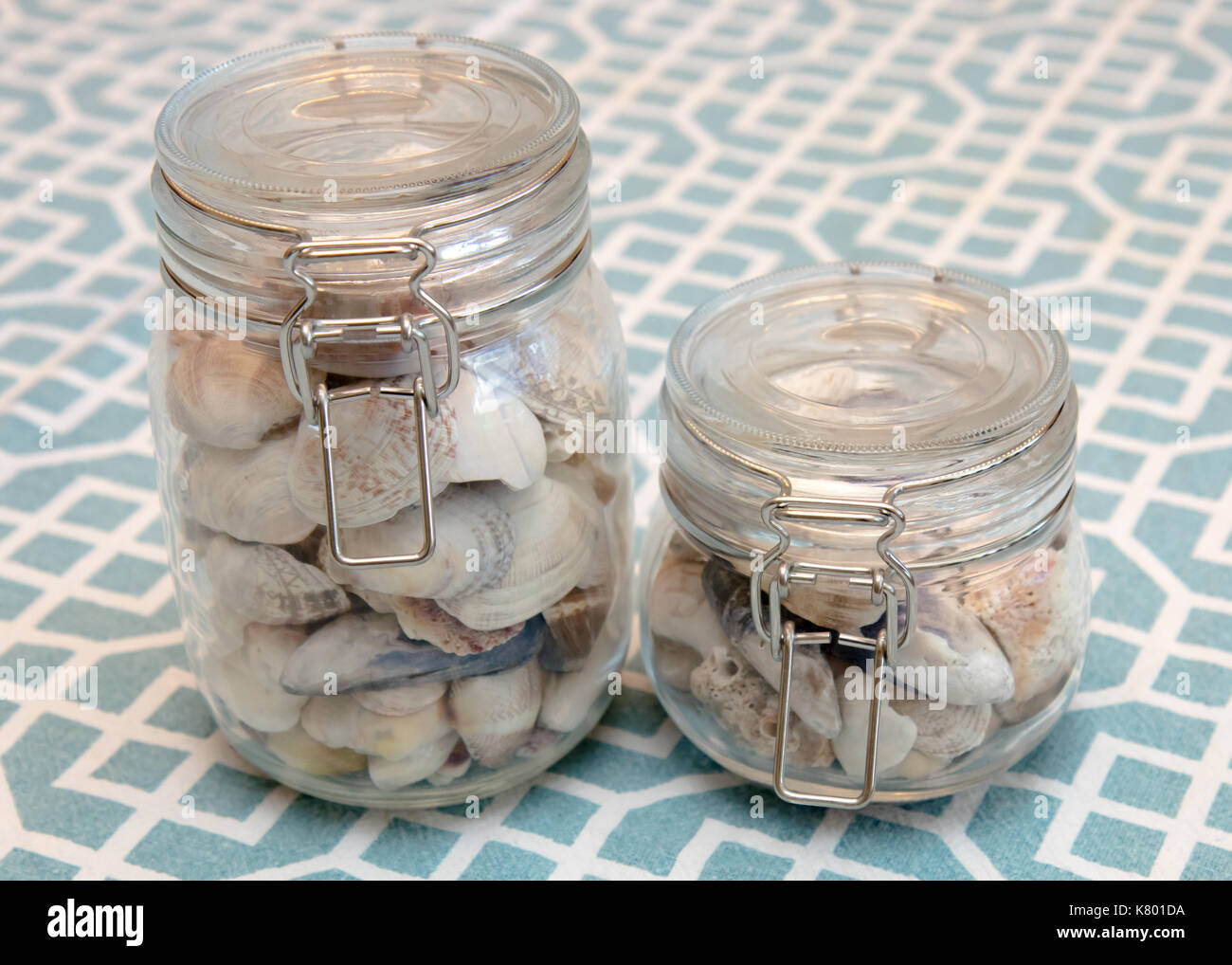 Two jars full of seashells sitting on a pretty blue tablecloth. - Stock Image