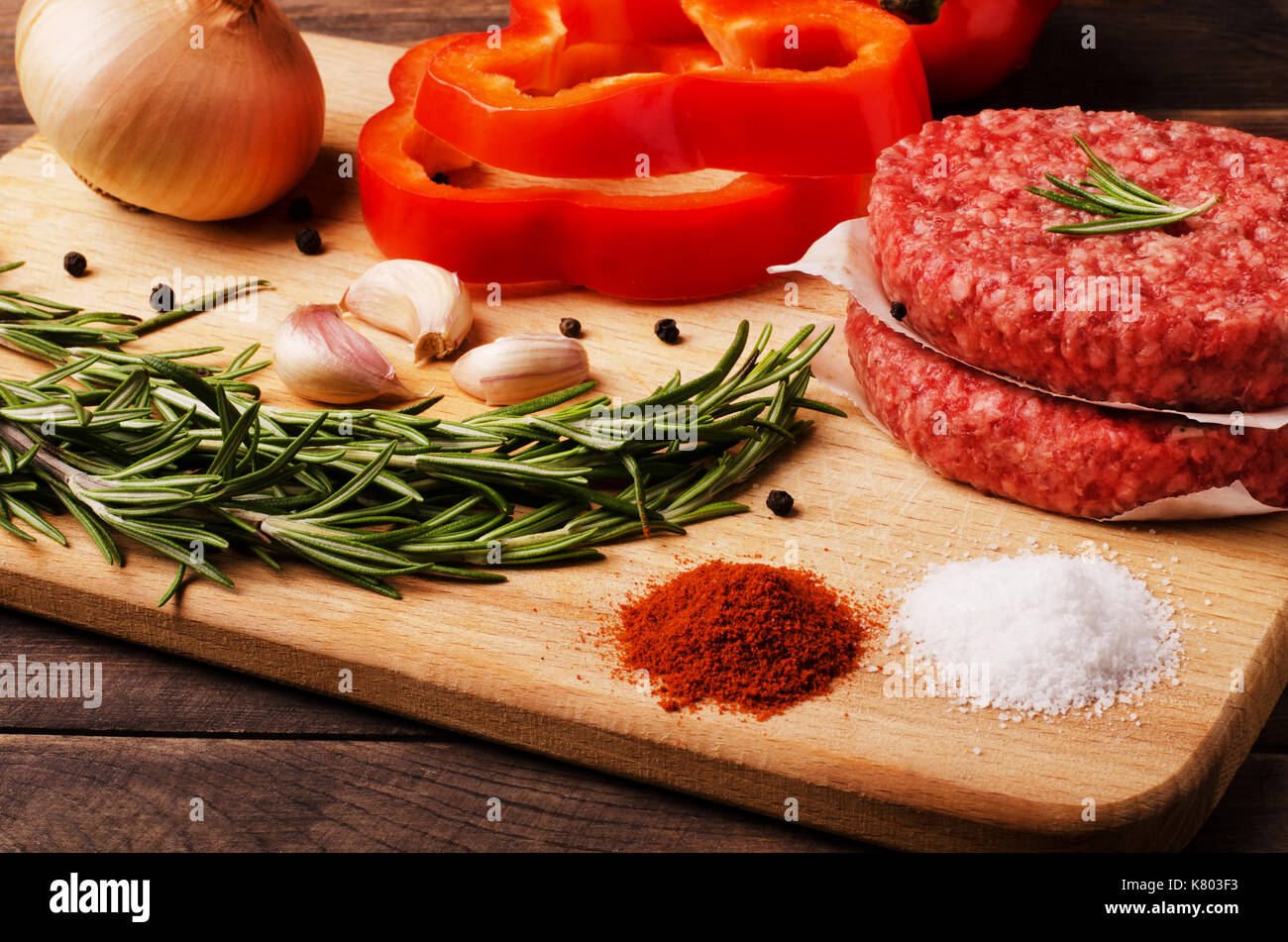 Raw ground beef burgers cutlets with red onion, garlic, olive and red pepper oil to prepare for frying in oven, close-up - Stock Image
