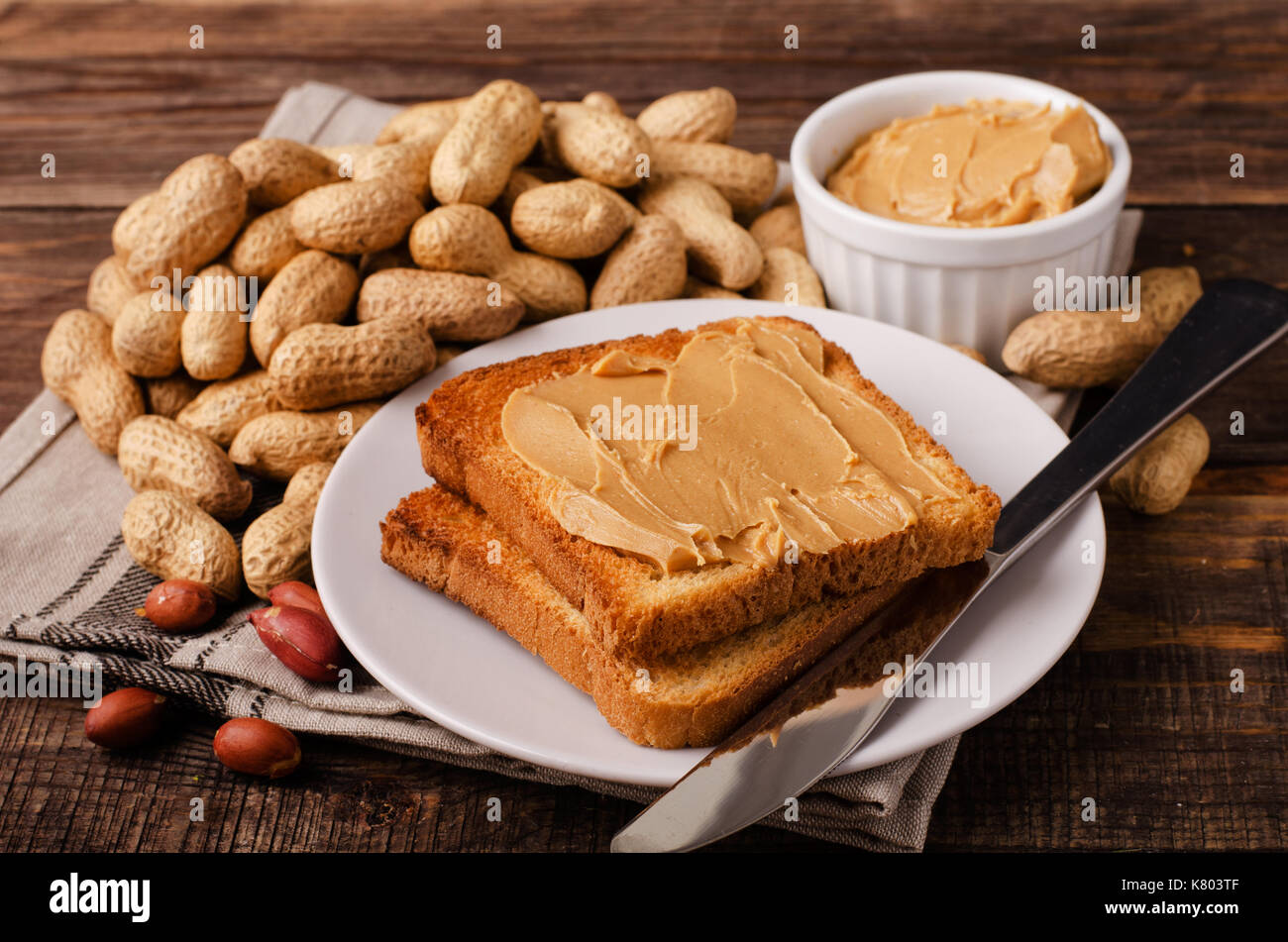 Peanut butter sandwich on plate with inshell peanuts, breakfast on the wooden background - Stock Image