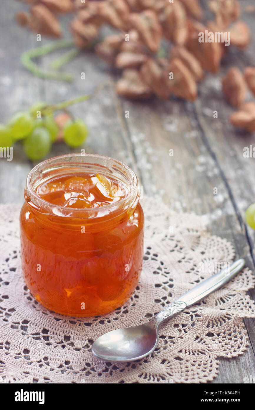 Slatko - white grape jam (sweet), traditional serbian desert; white grapes in syrup in a glass jar - Stock Image