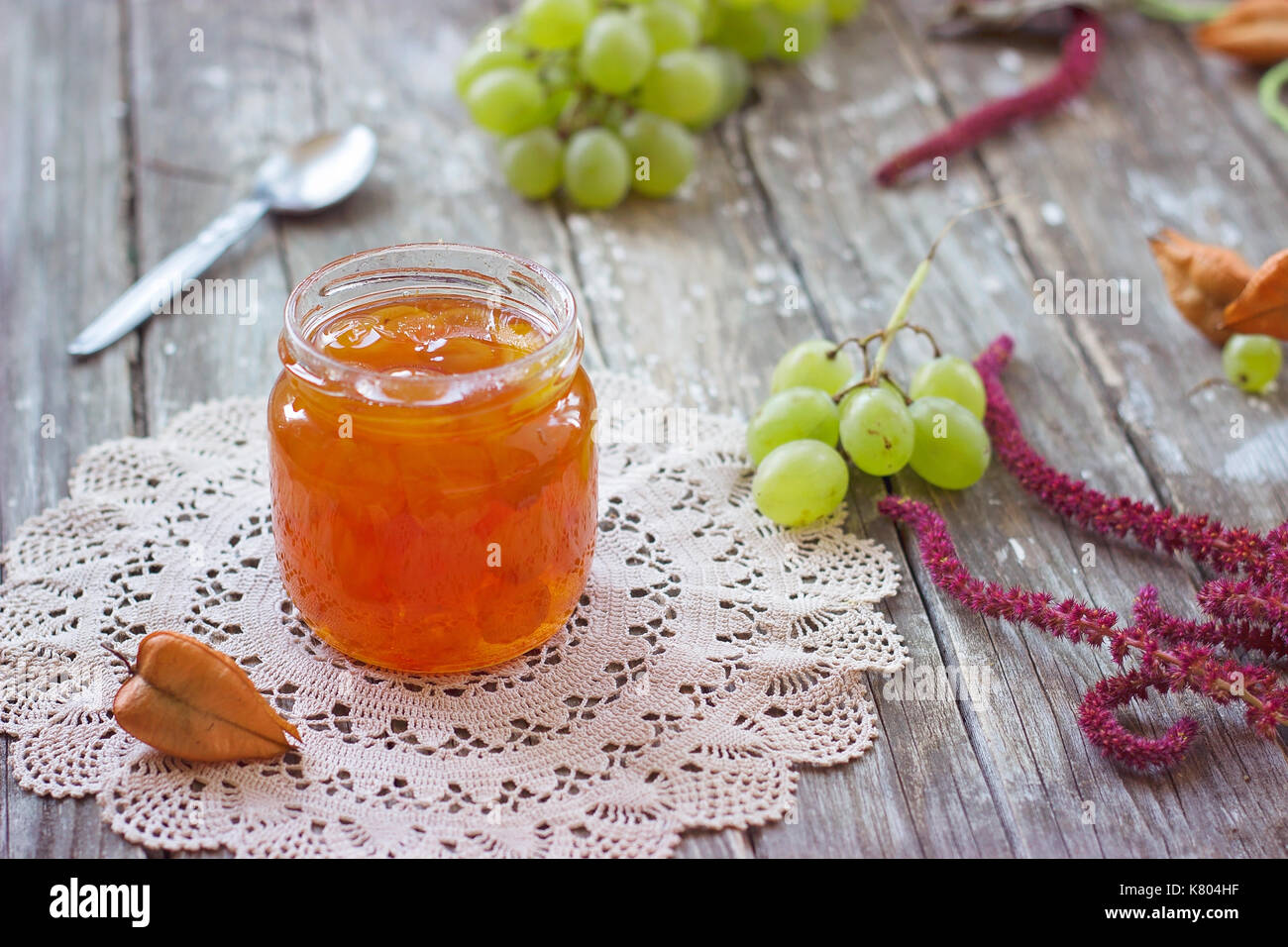 Slatko - preserved white grapes in glass jar, on wooden background; traditional serbian desert of white grapes or white cherries - Stock Image