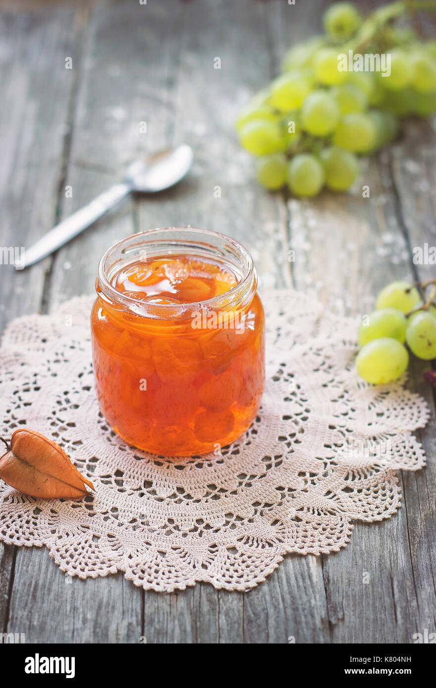 Slatko - preserved white grapes in glass jar, on wooden background; traditional serbian desert of white grapes or Stock Photo