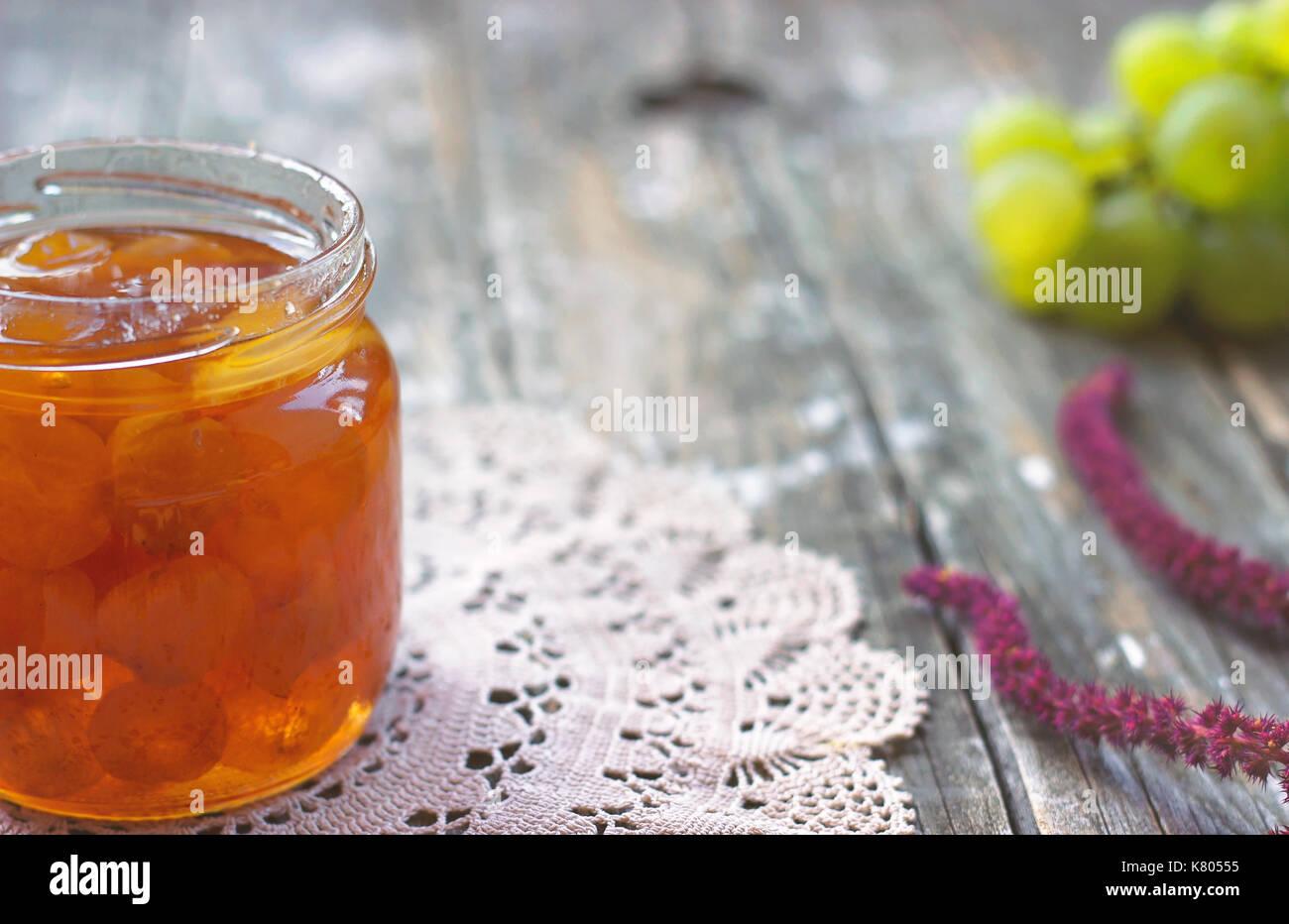 Slatko - preserved white grapes in glass jar, on wooden background; traditional serbian desert of white grapes or white cherries - Stock Image