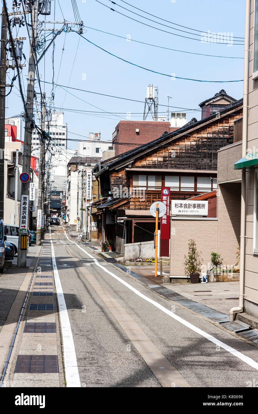 Typical Japanese narrow single lane street with buildings on both sides and many overhead electric cables. Empty, daytime. Kanazawa, Japan. - Stock Image