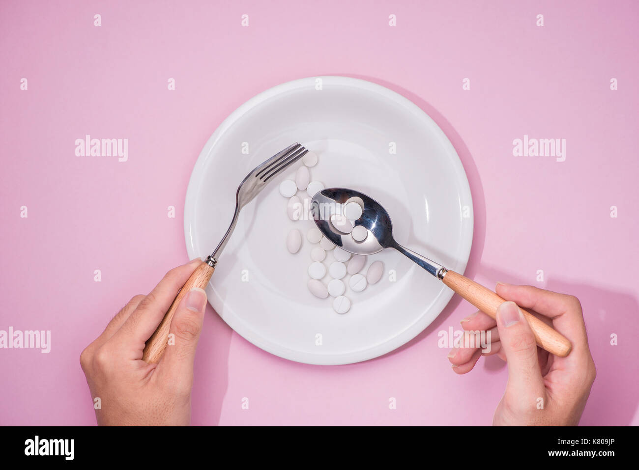 Top view of man's hands at dining table holding a fork and knife above dish with pills over pink background. - Stock Image