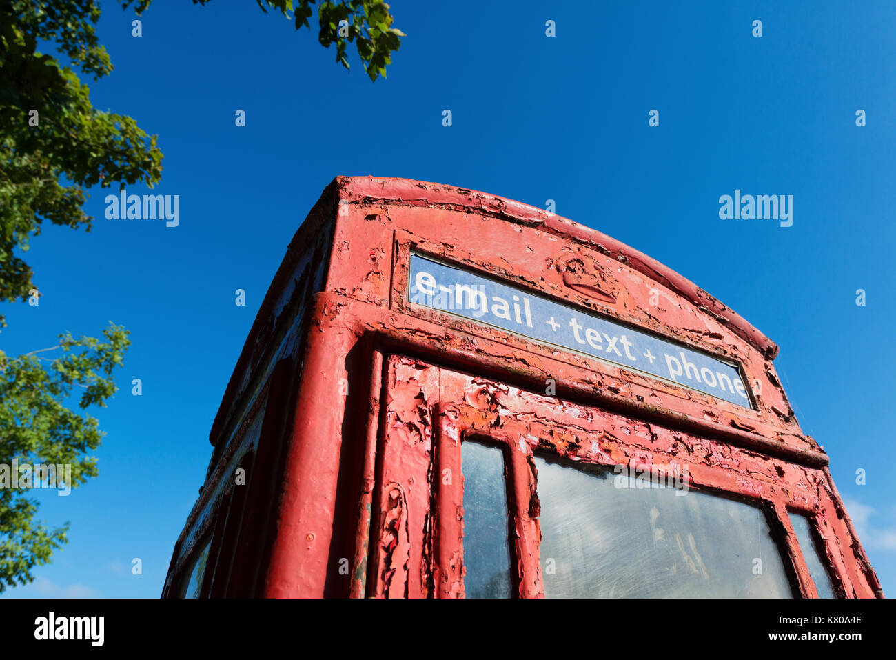 Rusty and Peeling Old Red Telephone Box against a Blue Sky - Stock Image