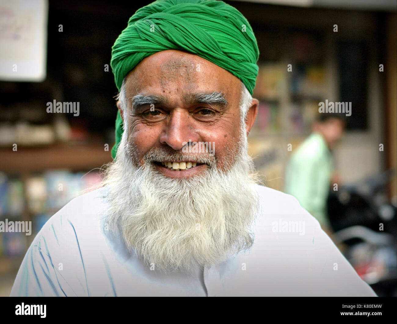 Smiling, elderly Indian Muslim man with white Muslim full-beard and distinctive Muslim prayer bump (zebibah) on his forehead, wearing a green turban - Stock Image