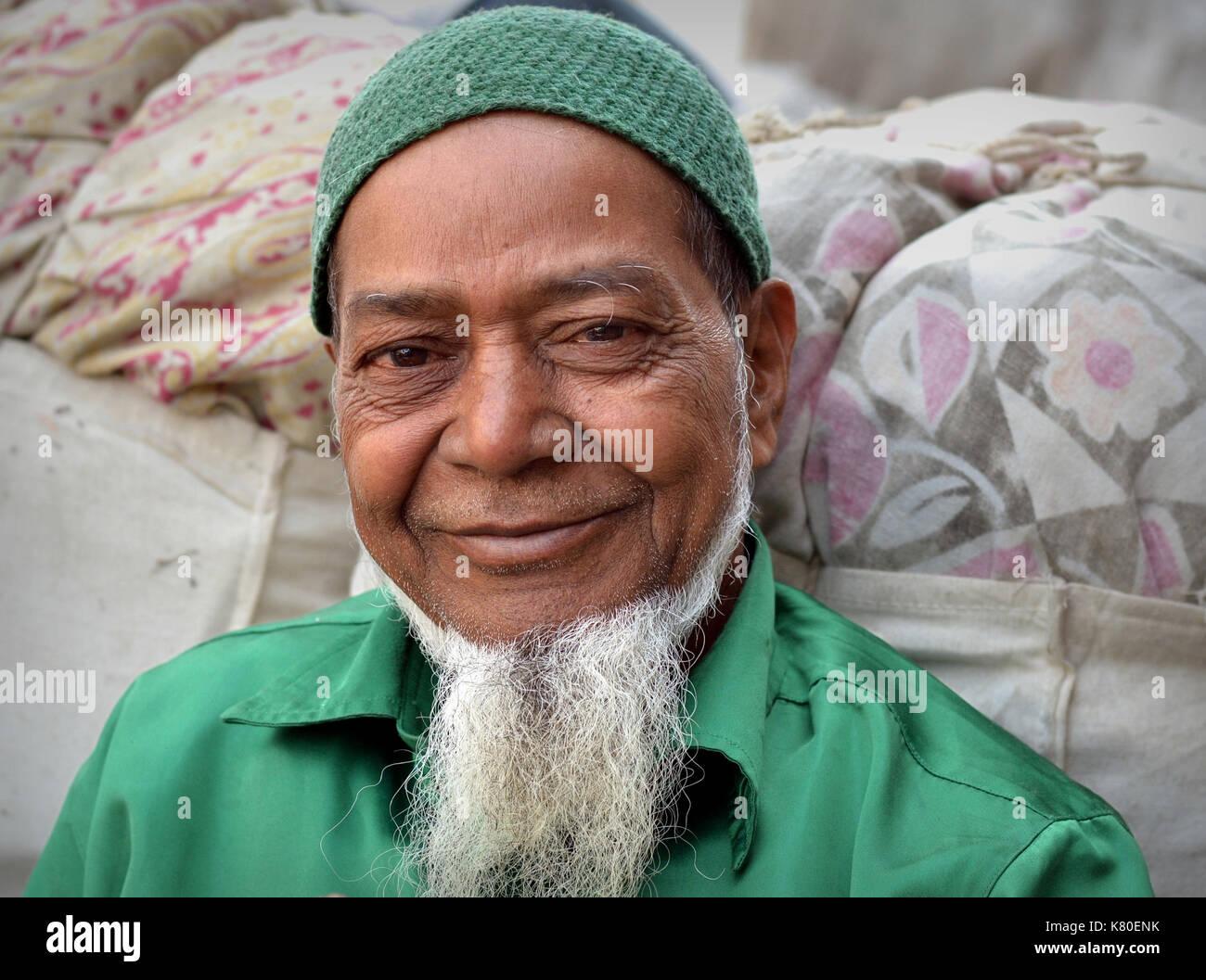 Elderly Indian Muslim man with white Muslim chin beard, wearing a green shirt and a knitted green Muslim prayer cap (taqiyah) - Stock Image