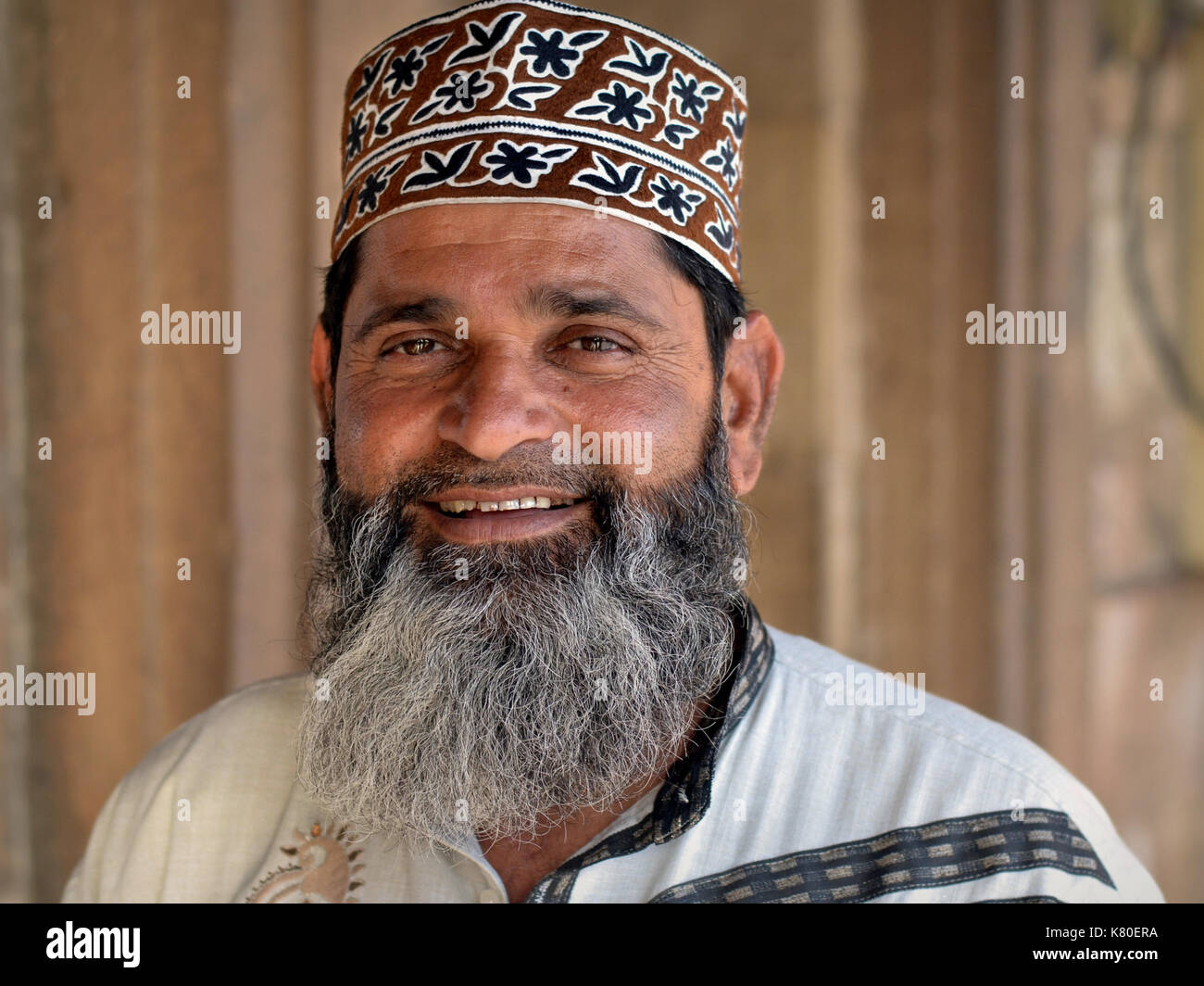 Middle-aged Indian Muslim man with Muslim-style trimmed full beard, wearing a patterned Islamic prayer cap (taqiyah) from Oman - Stock Image