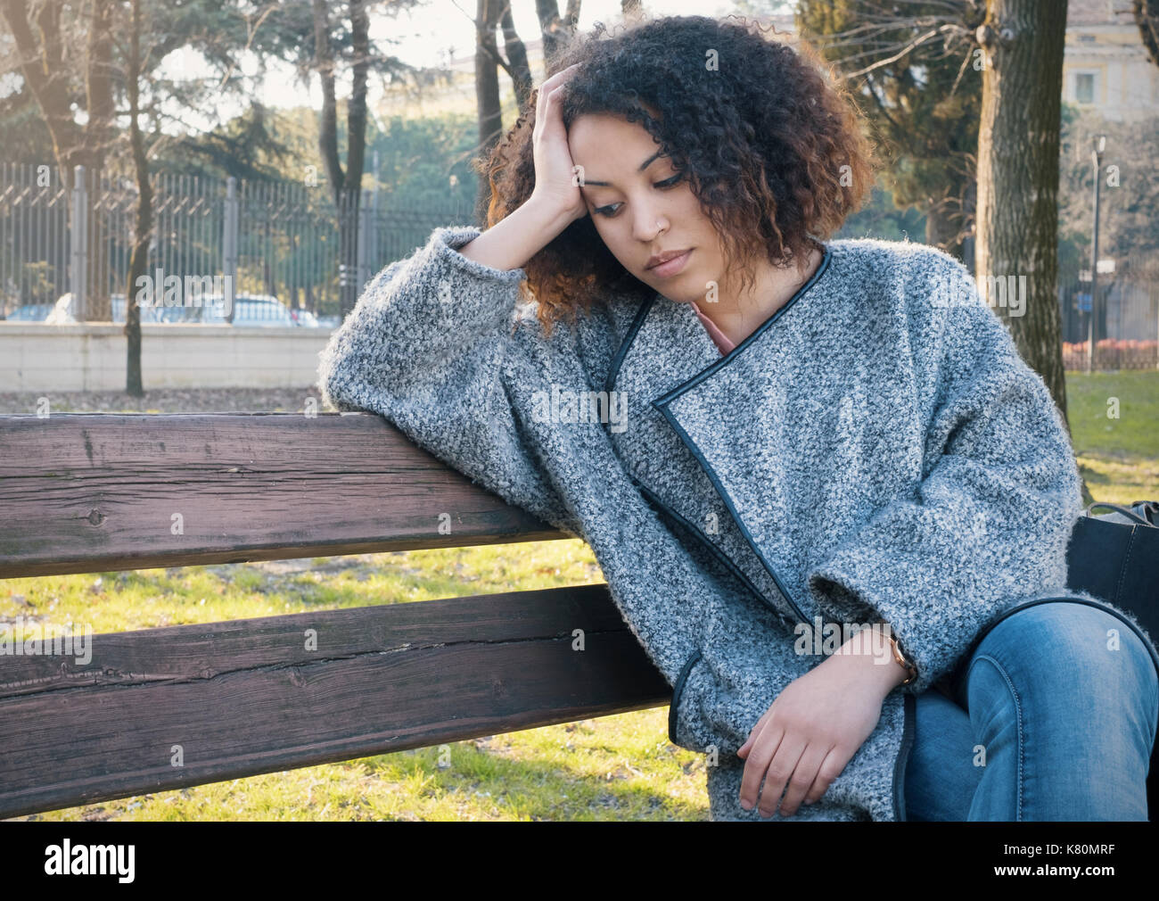 Sad black woman seated alone on a bench at the park - Stock Image