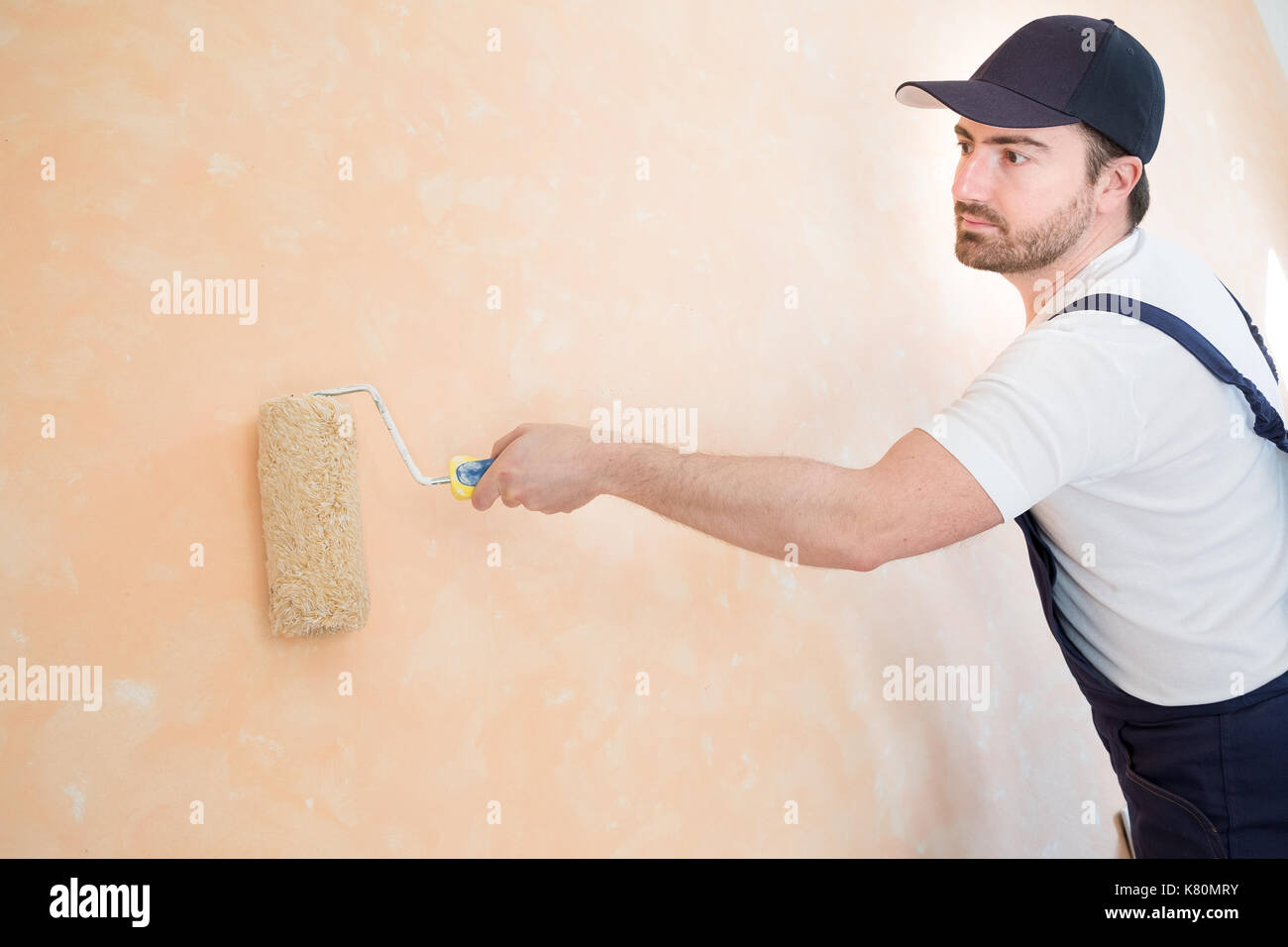 Professional painter worker is painting a wall - Stock Image