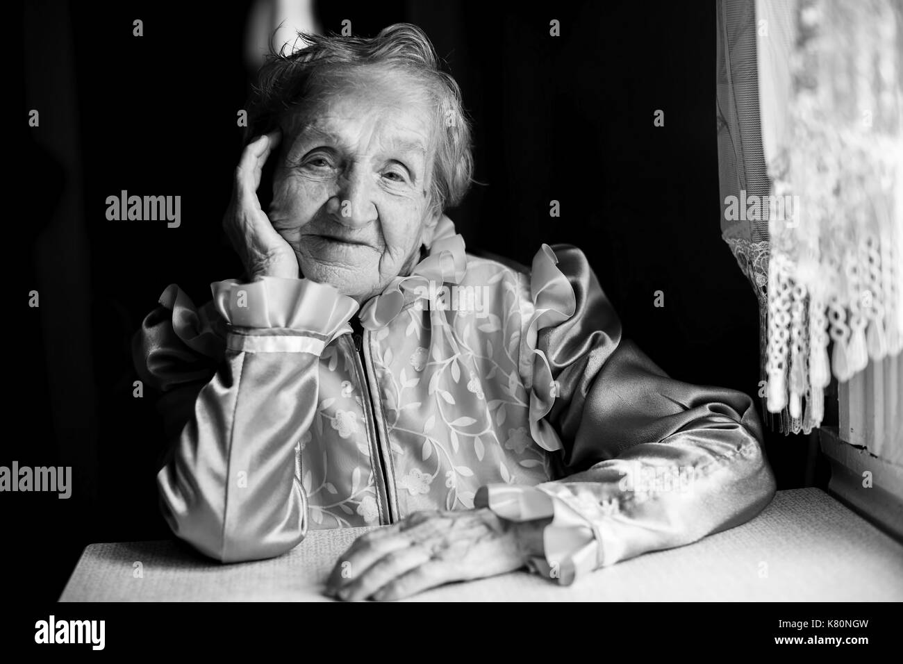 Portrait of a Slavic grandmother at the table in the house. Black-and-white picture. - Stock Image
