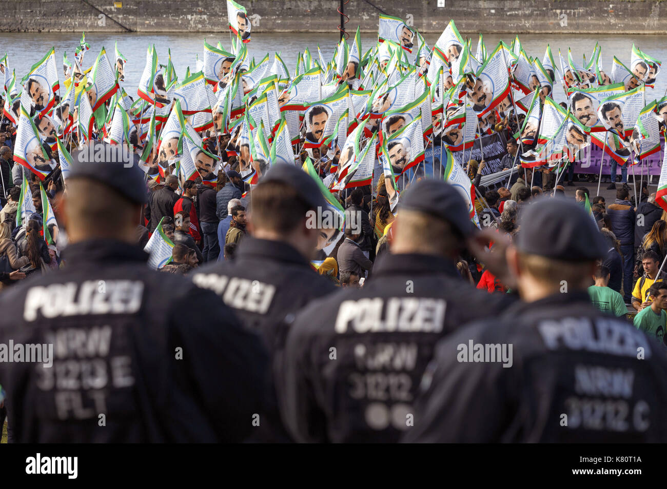 Cologne, Germany. 16th Sep, 2017. Participants of the international Kurdish culture festival wave flags showing Öcalan, the leader of the Kurdistan Workers' Party (PKK), at the Deutzer shipyard in Cologne, Germany, 16 September 2017. Police officers observing the situation can be seen in the foreground. Turkey ordered the German ambassador in Ankara to the Foreign Ministry protesting against the Kurdish festival in Cologne. Photo: Christoph Hardt/Geisler-Fotopres/Geisler-Fotopress/dpa/dpa/Alamy Live News - Stock Image