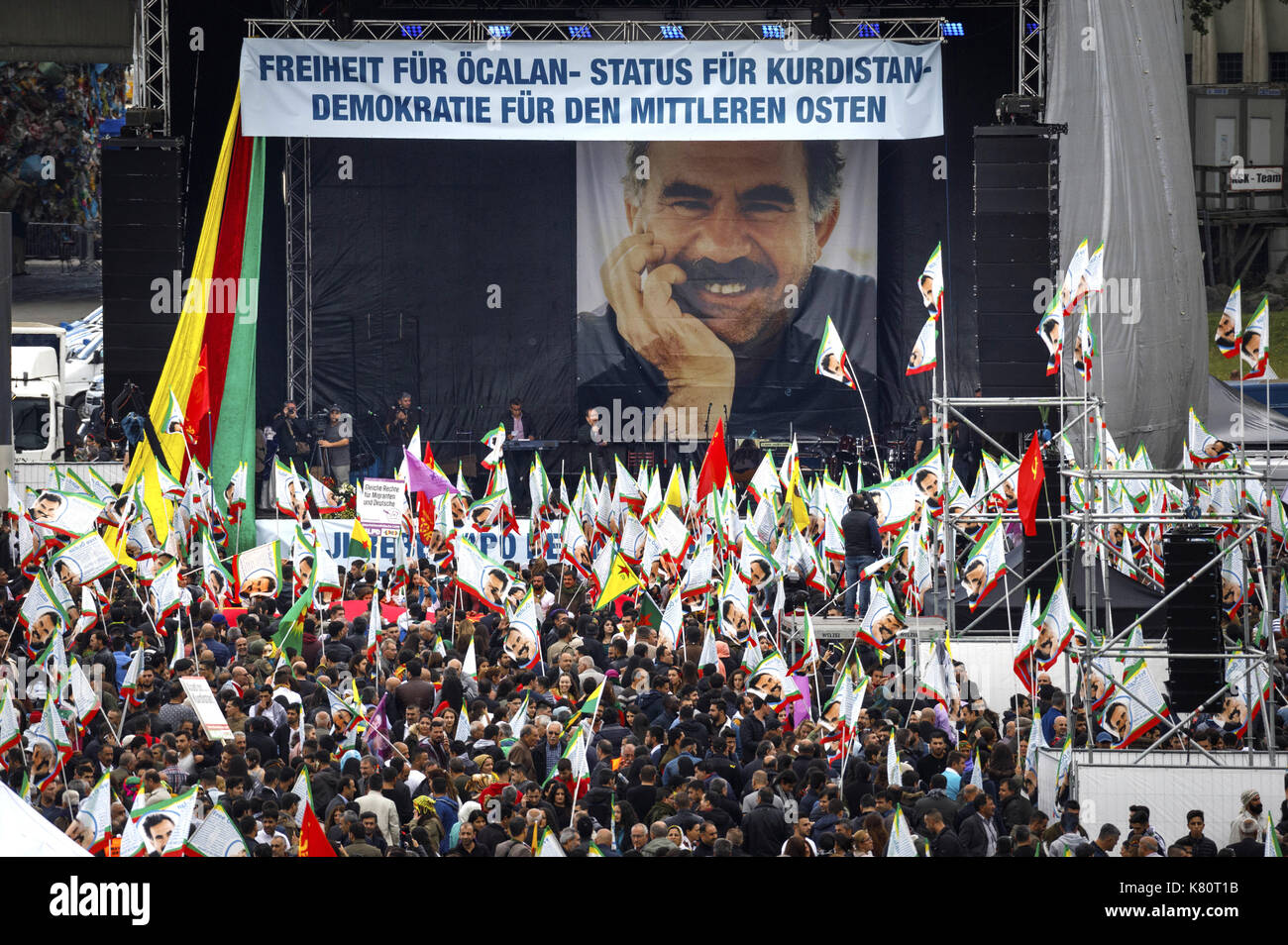 Cologne, Germany. 16th Sep, 2017. Participants of the international Kurdish culture festival wave flags in front of the stage with a huge picture of Öcalan, the leader of the Kurdistan Workers' Party (PKK), at the Deutzer shipyard in Cologne, Germany, 16 September 2017. Turkey ordered the German ambassador in Ankara to the Foreign Ministry protesting against the Kurdish festival in Cologne. Photo: Christoph Hardt/Geisler-Fotopres/Geisler-Fotopress/dpa/dpa/Alamy Live News - Stock Image