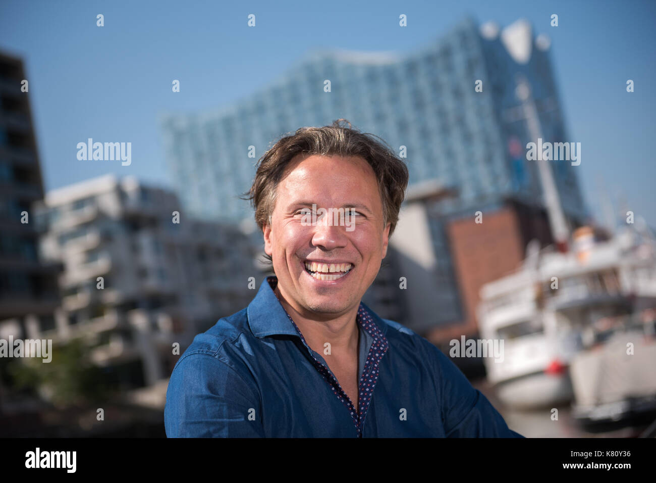 Hamburg, Germany. 29th Aug, 2017. dpa Exclusive - Pianist and conductor Kristjan Jaervi pictured at HafenCity in Hamburg, Germany, 29 August 2017. The Elbphilharmonie (Elbe Philharmonic Hall) can be seen in the background. Photo: Daniel Bockwoldt/dpa/Alamy Live News - Stock Image