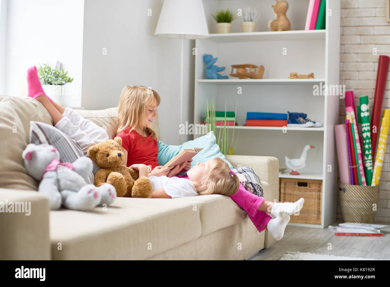 Reading Aloud to Little Sister - Stock Image