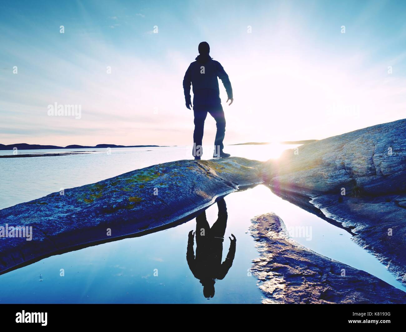 Tall backpacker watch clear sunny spring daybreak over sea. Hiker with backpack stand on rocky shore and his figure is mirrored in water pool.  Hiker  - Stock Image