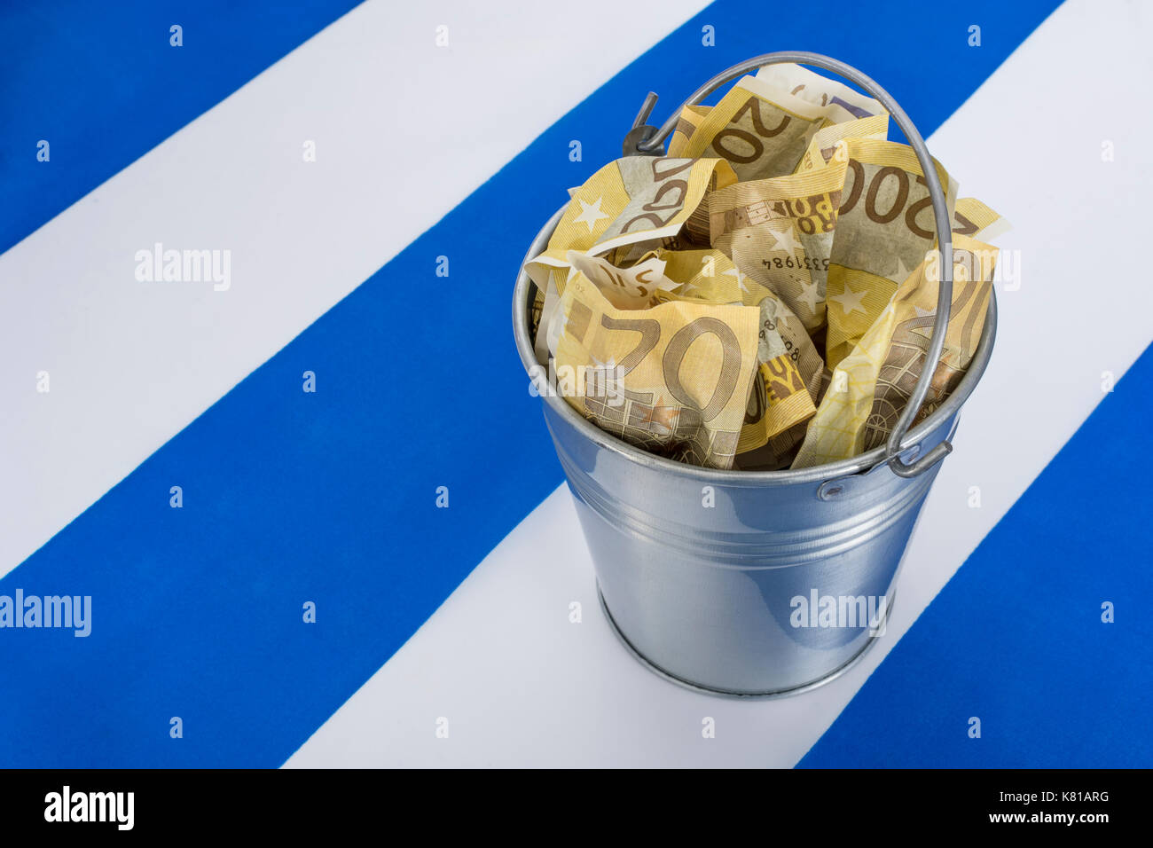 Greek flag with a metal bucket of 200 Euro banknotes - as metaphor for the Greek financial crisis and bailout, Greek debt relief. - Stock Image