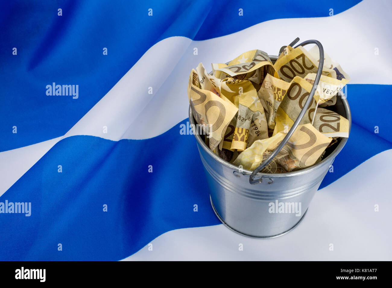 Greek flag with a bucket of Euros - as metaphor for the Greek financial crisis and bailout, Greek debt relief. - Stock Image