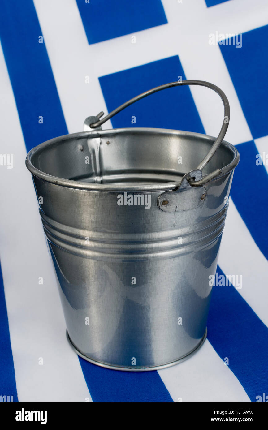 Greek flag with an empty metal bucket - as metaphor for the Greek financial crisis and bailout, Greek debt relief. - Stock Image