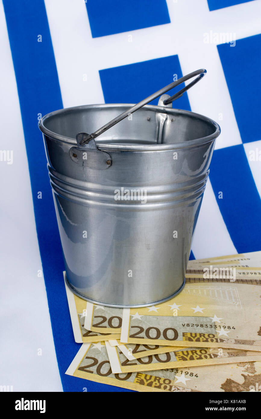 Greek flag with a metal  bucket and 200 Euro banknotes - as metaphor for the Greek financial crisis and bailout, Greek debt relief. - Stock Image