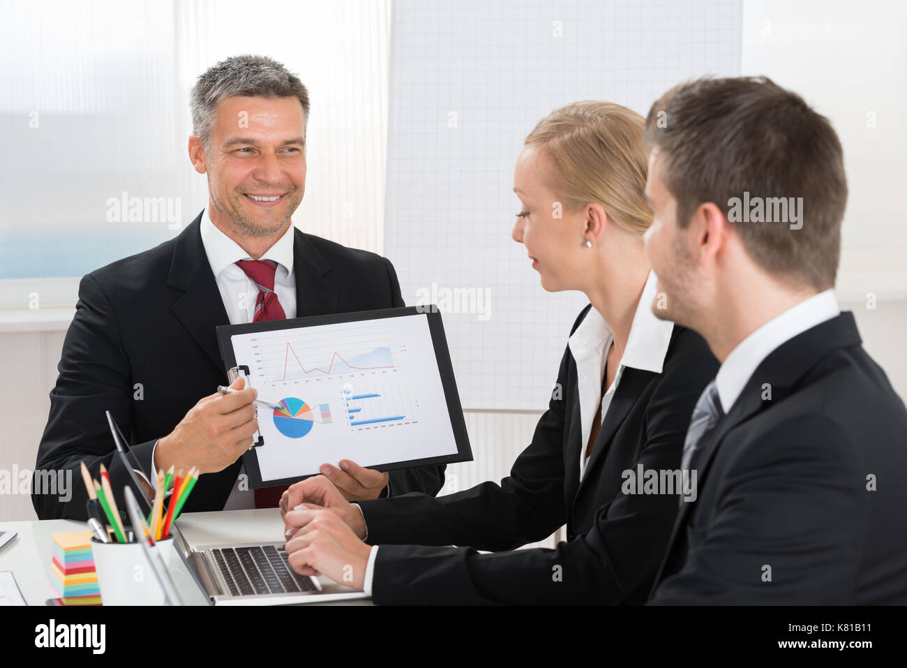 Mature Businessman Explaining Graph To His Co- Workers In Office - Stock Image
