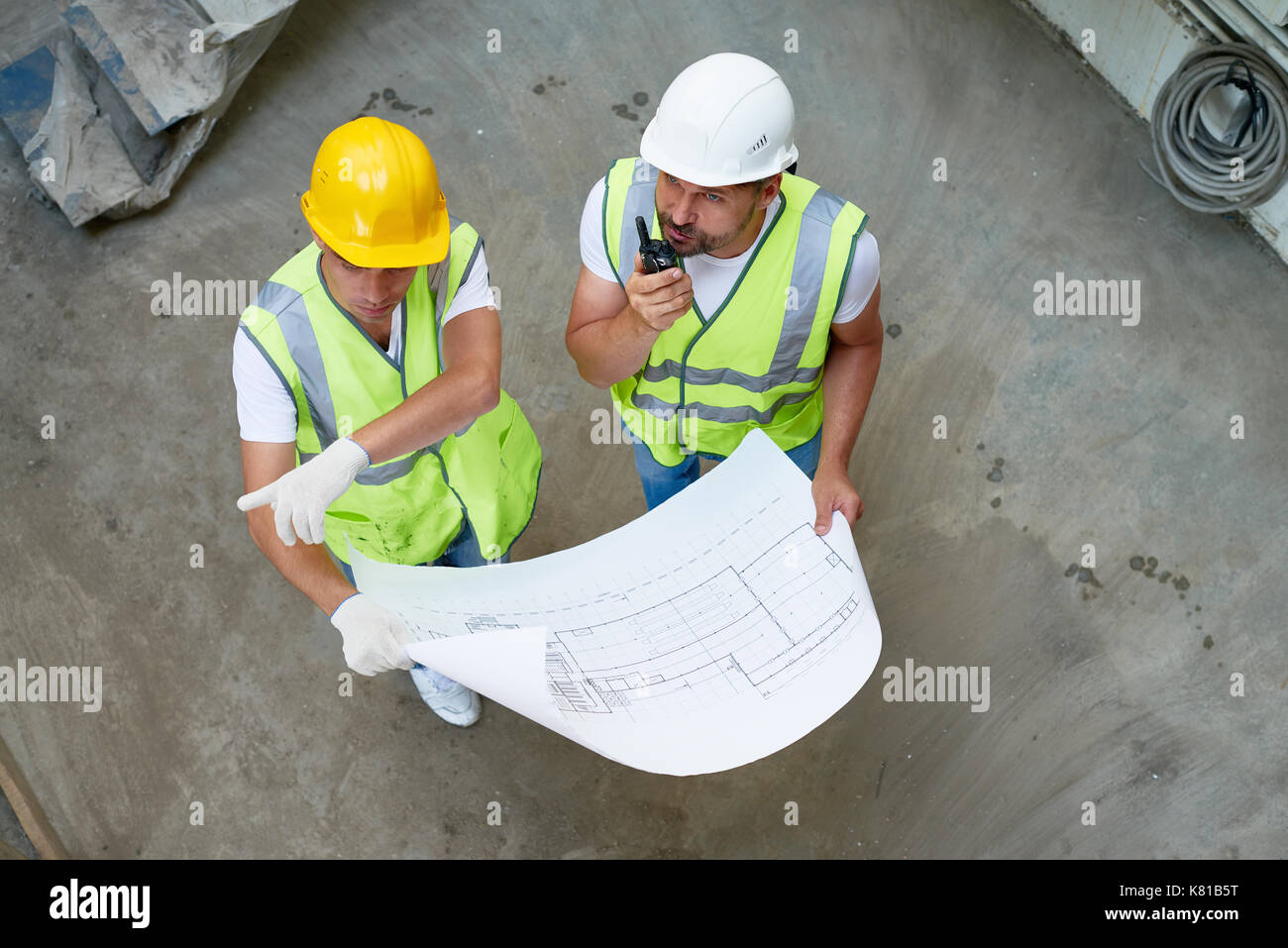 Construction Workers Wrapped up in Discussion - Stock Image