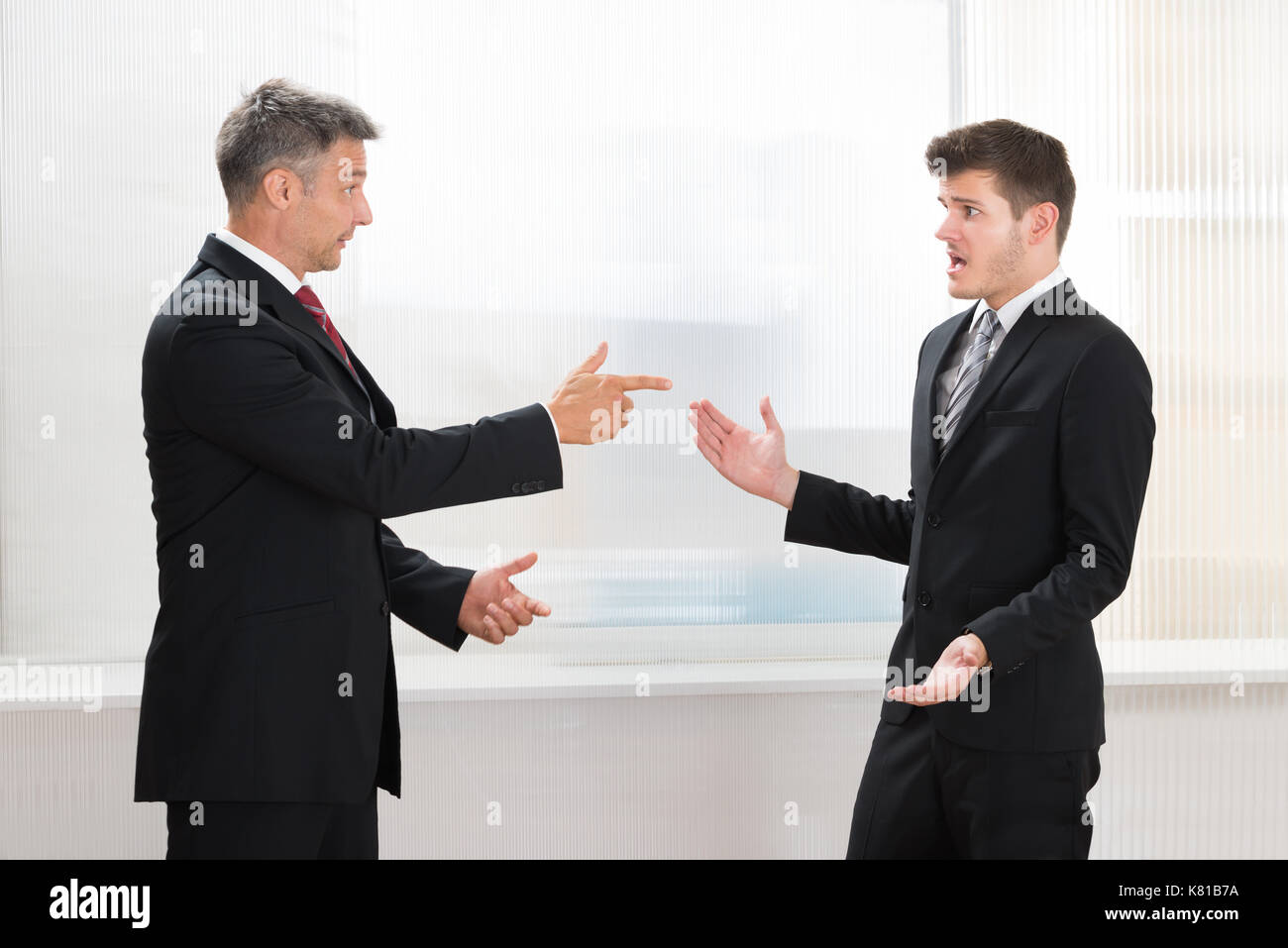 Two Businessmen Quarreling With Each Other In Office - Stock Image