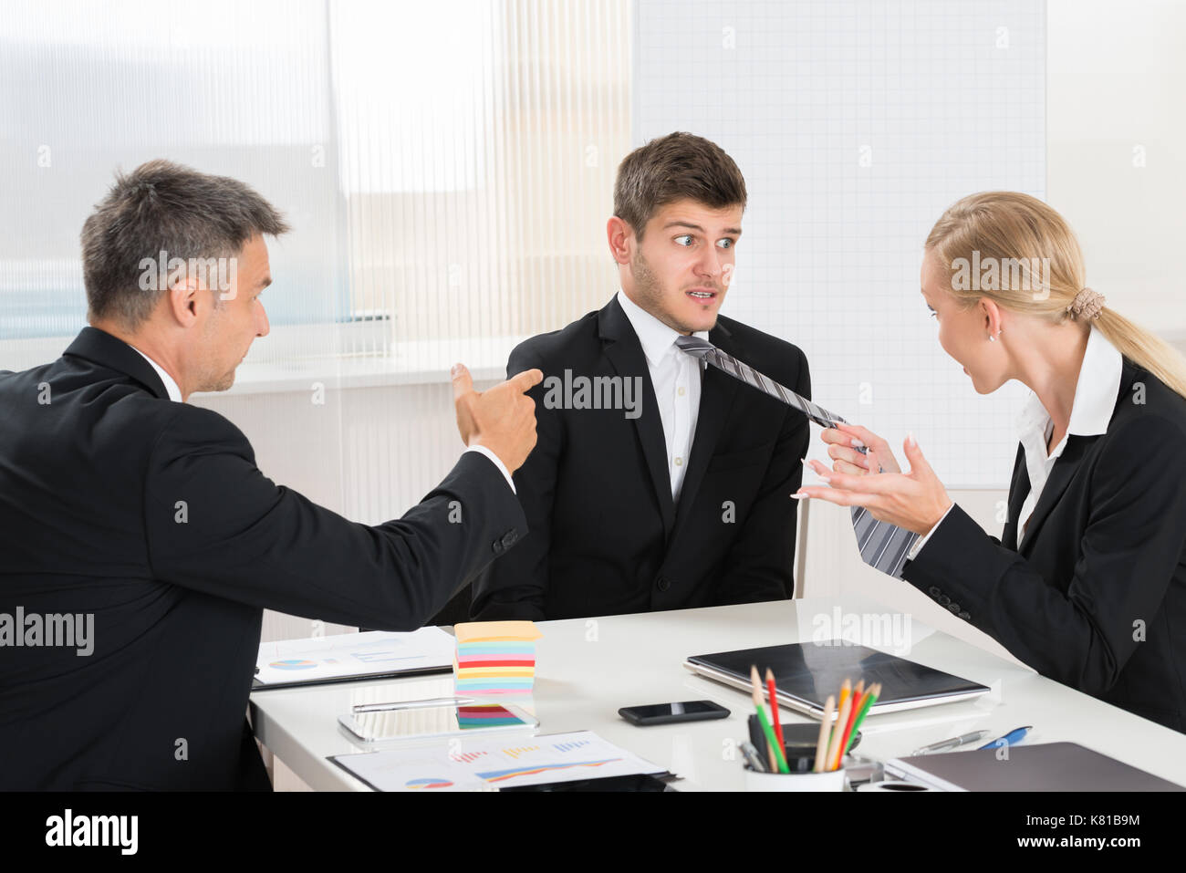 Two Businesspeople Quarreling To Young Businessman At Desk In Office - Stock Image