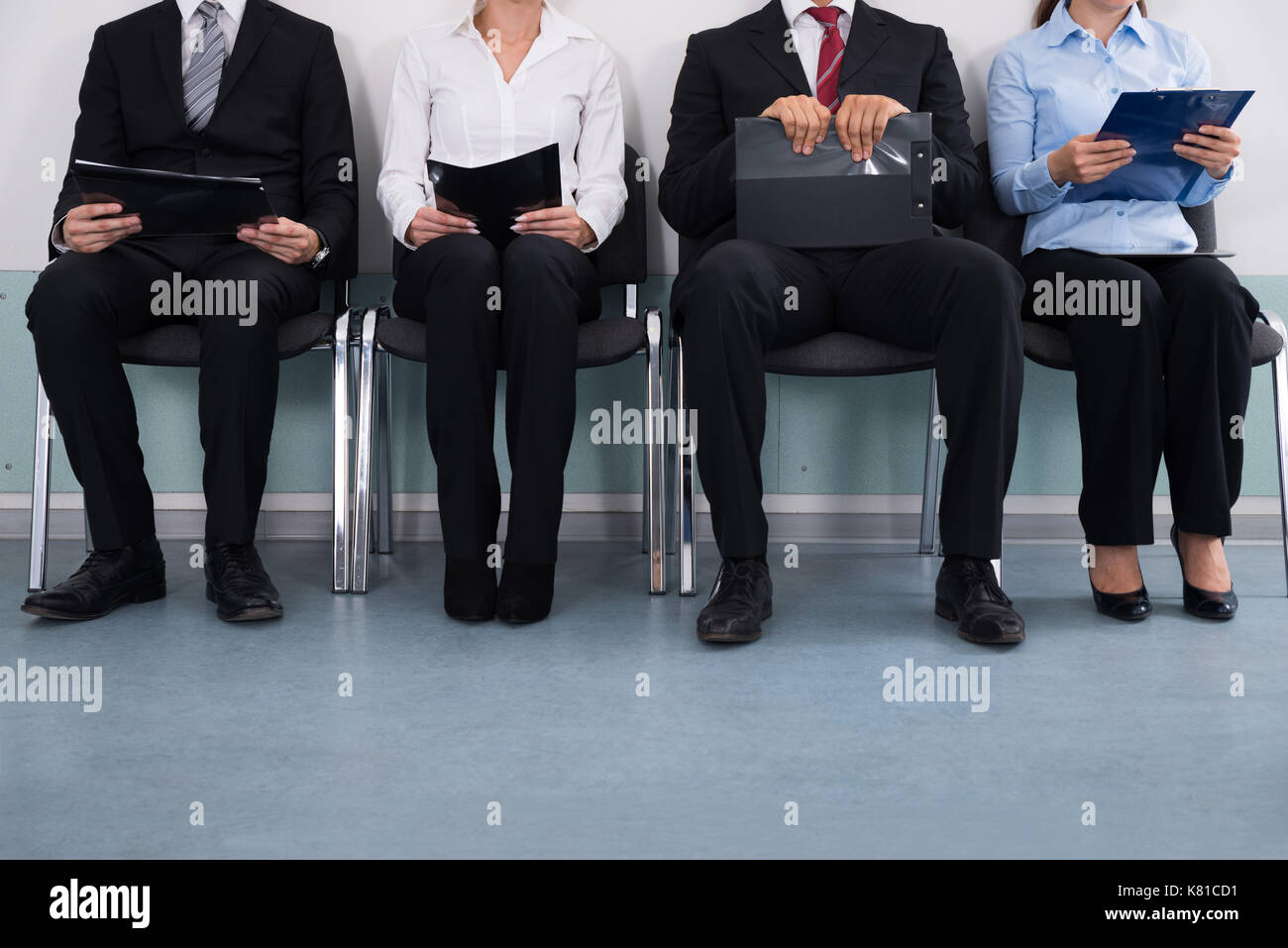 Close-up Of Businesspeople With Files Sitting On Chair - Stock Image