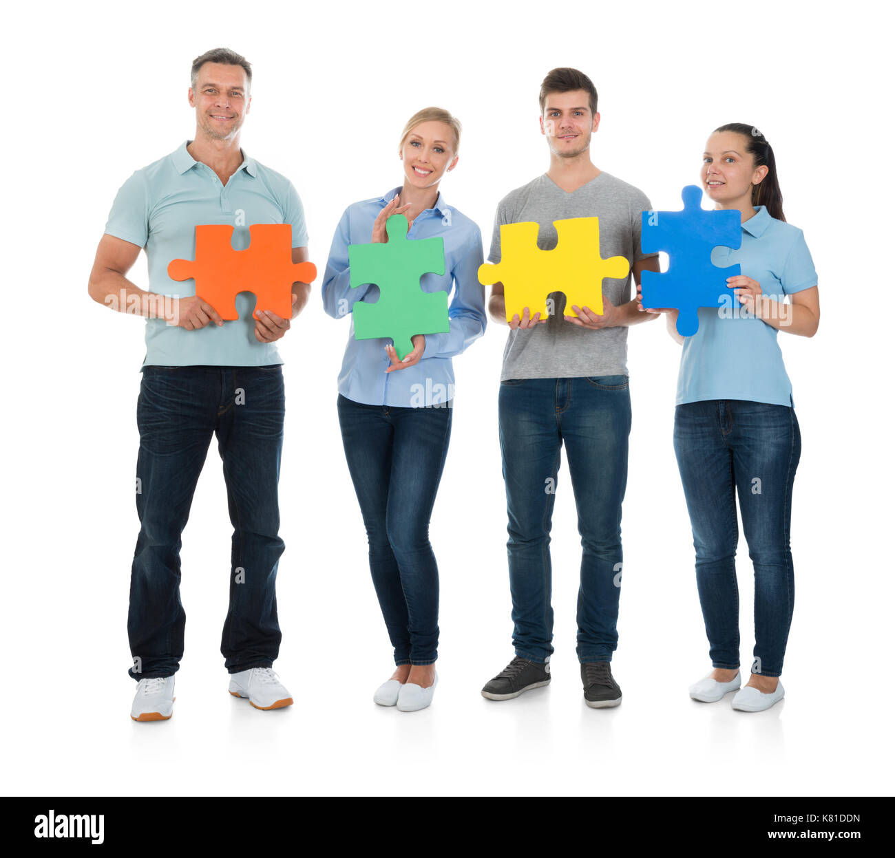 Group Of Happy People Holding Colorful Jigsaw Pieces Over White Background - Stock Image