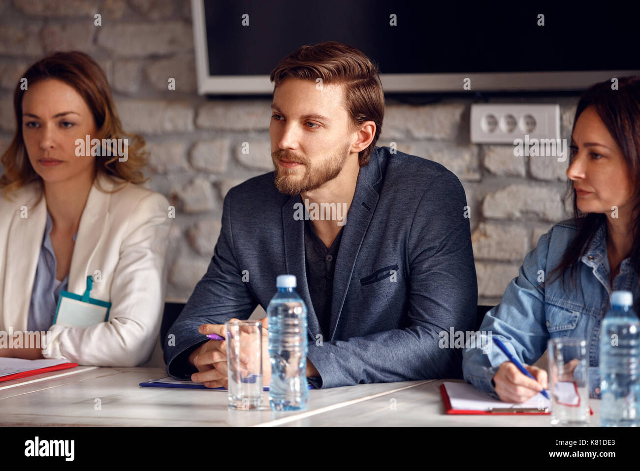 Serious man with two female colleagues in commission for employment in company - Stock Image