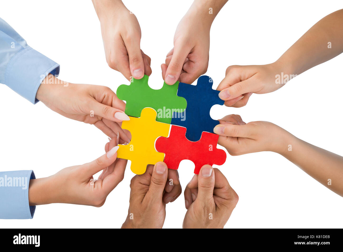 Close-up Of People Hands Holding Jigsaw Pieces Over White Background - Stock Image